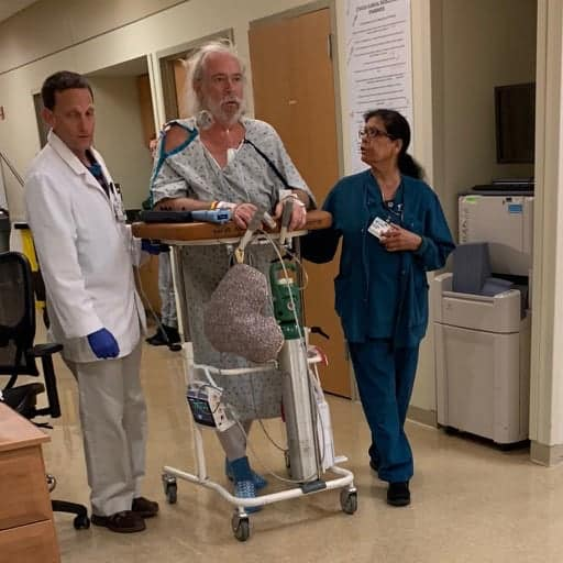 Larry in the hospital walking after surgery