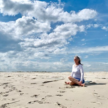 Theresa on the beach yoga pose with clouds overhead