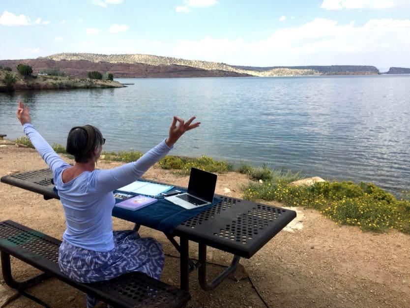 Theresa sitting at a table near a lake teaching telewellness