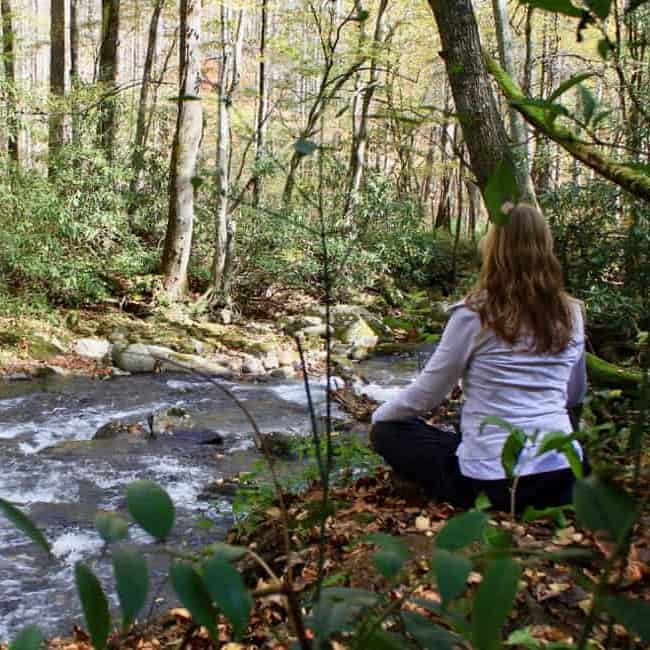 Yogi Theresa Macy, practicing beside a stream.