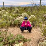 Theresa squatting in the Tucson desert
